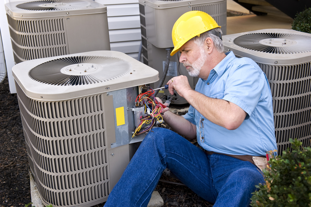 Photo of repairman doing air conditioning unit maintenance